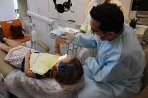 Dentist performing cleaning on patient